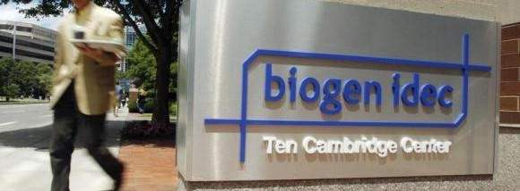 A pedestrian passes the sign outside the headquarters of Biogen Idec Inc. in Cambridge